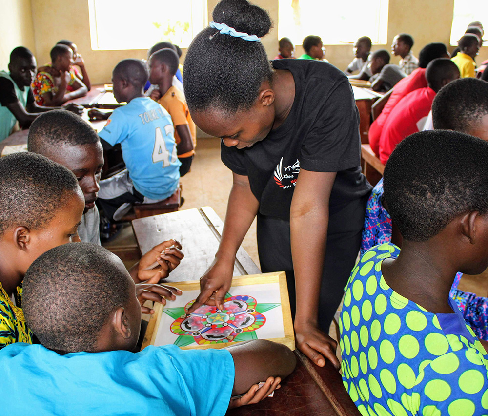 Tisiya Mahoro, standing, helps students at Kinakyeitaka Primary School in Uganda play the 5 STA-Z board game developed by UW–Madison engineering students.